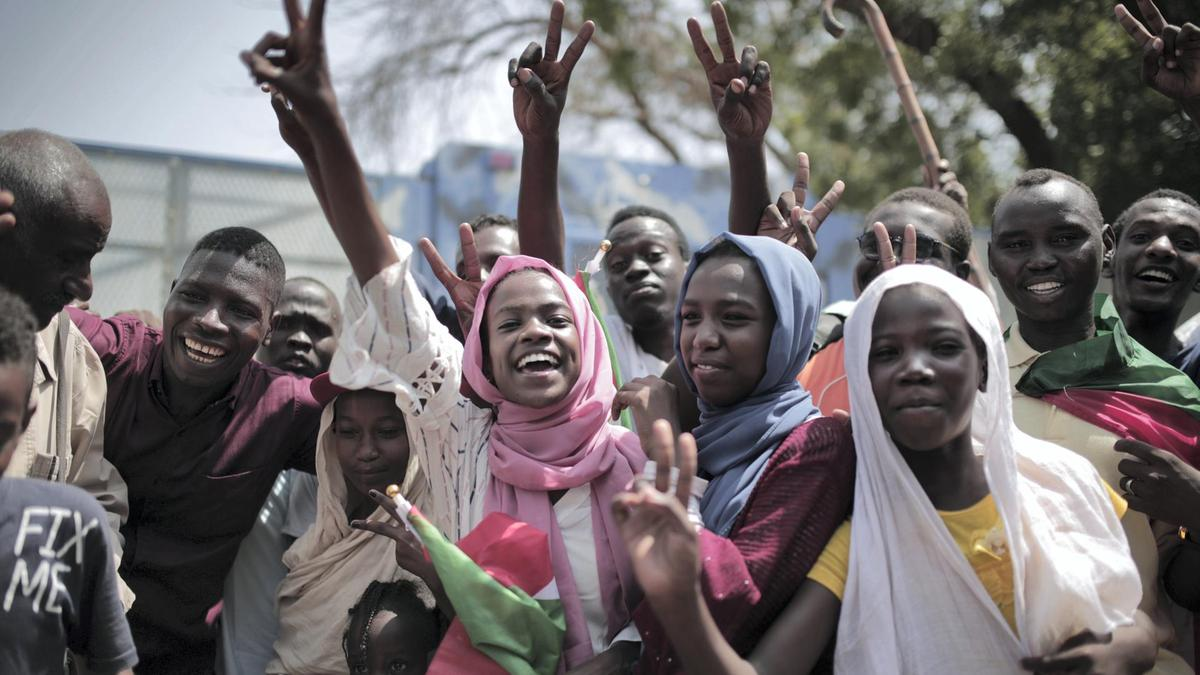 Sudanese women and men celebrate in Khartoum on 17 August 2019 after generals and protest leaders signed a transitional constitution. AFP.