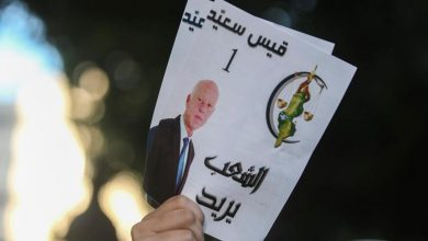 A supporter of Tunisian President Kais Saied holding a promotional flyer during the presidential elections he won, 19 October 2019. AP, Mosa'ab Elshamy