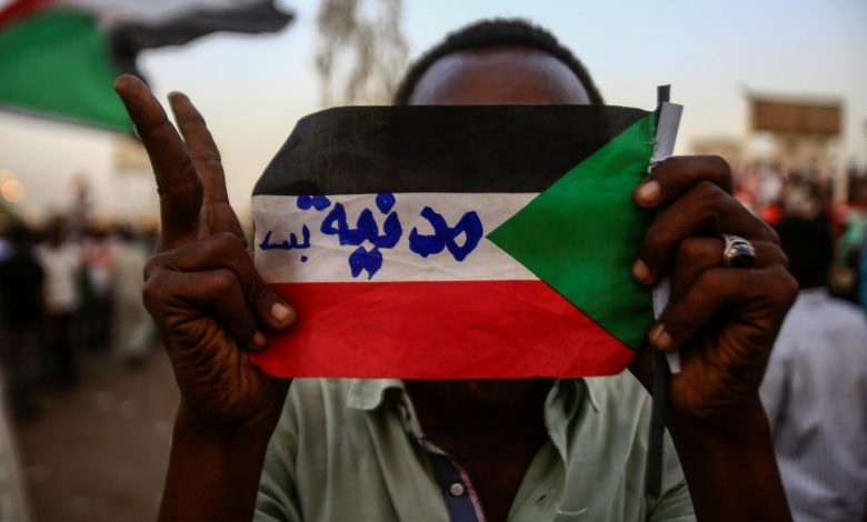 "A Sudanese protester holds the national flag with writings reading in Arabic ""Civilian Only"" during a rally outside the army headquarters in Khartoum on 2 May 2019. AFP."