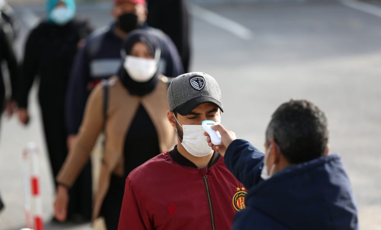 A security guard measures the temperature of workers in line in a factory in Manouba after the announcement of total containment on 22 March 2020 against the pandemic of CoViD-19, Tunisia, 14 April 2020. Reuters, Mohamed Krit.