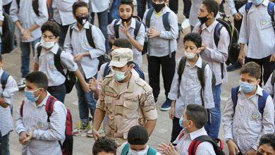 An army member wearing a protective mask stands guard between students as they attend the first day at Al Saadeya school, following months of closure due to the Covid-19 outbreak, Cairo, Egypt, 17 October 2020. Reuters, Mohamed Abd El Ghany.