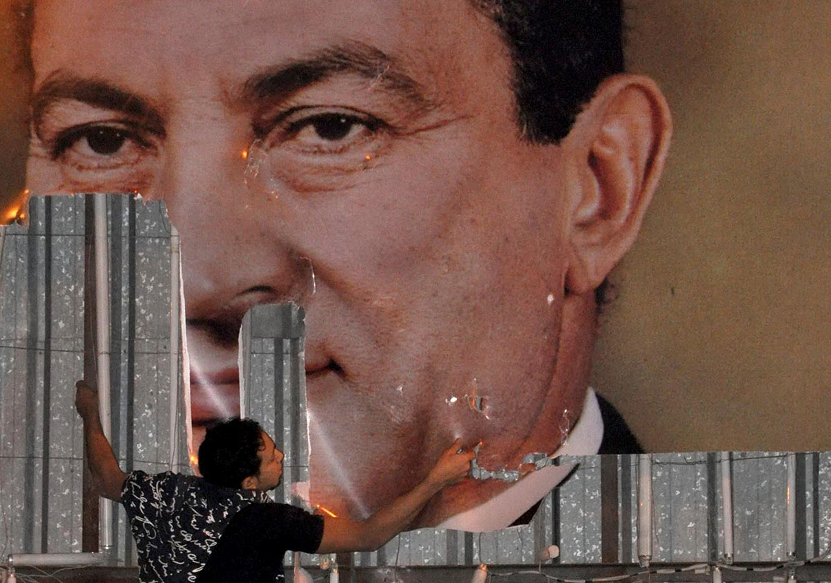 An anti-government protester defaces a picture of Egypt's President Hosni Mubarak in Alexandria, north of Cairo, Egypt, 25 January 2011. Reuters, Stringer, File Photo.