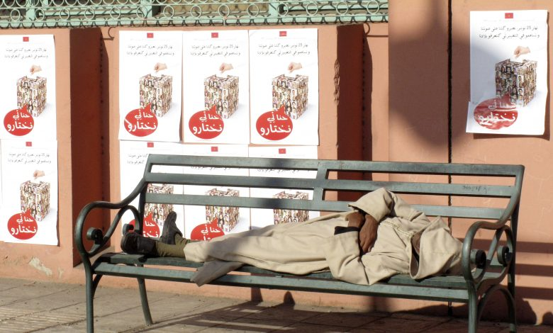 """A man sleeps near posters that read """"We can make a choice"""" before the Moroccan parliamentary elections of 25 November 2011, Marrakech, 18 November 2011. Reuters, Jean Blondin."""
