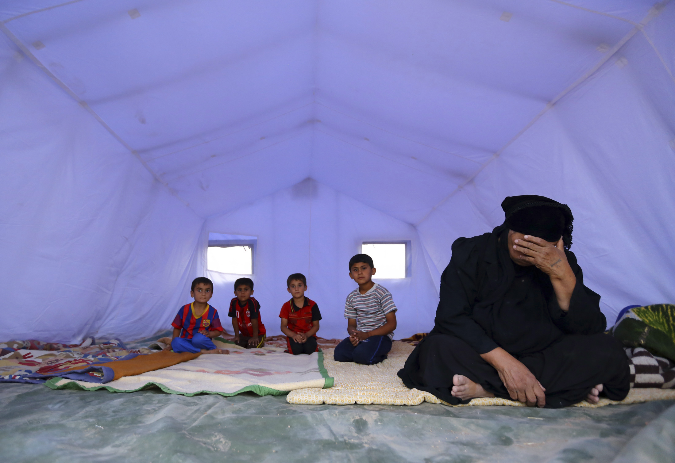 An Iraqi family, which fled from the violence in Mosul following the city's fall to ISIL, sits inside a tent at a camp on the outskirts of Arbil in Iraq's Kurdistan region, 12 June 2014. Reuters, stringer.